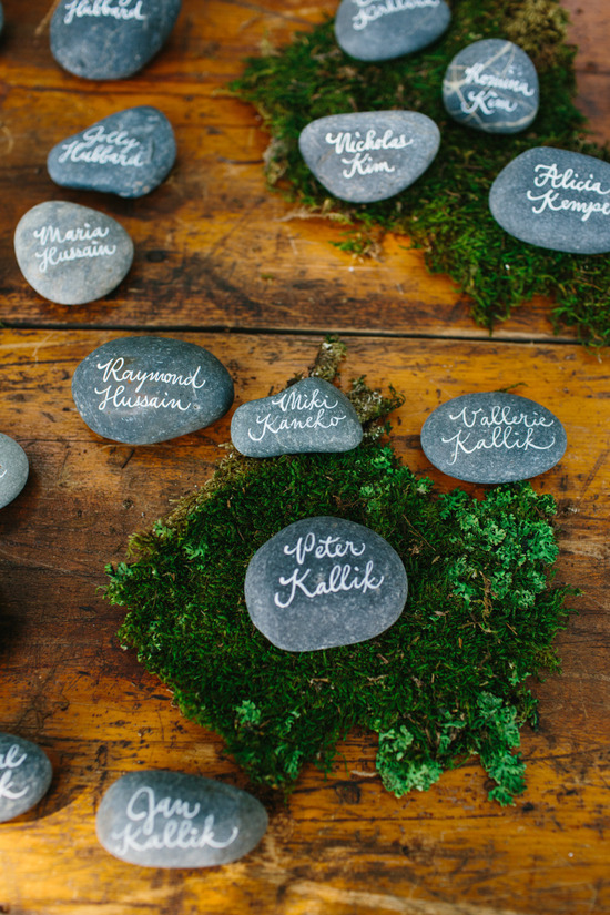stone escort cards displayed on mossy wood table