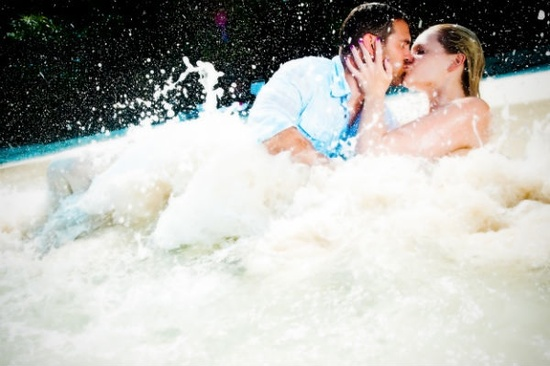 Bride and groom kiss as waves rush over them during tropical trash the dress shoot