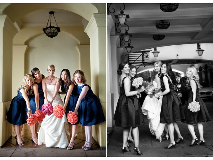 Bridesmaids in navy blue dresses hold coral rose bouquets, pose with blushing bride