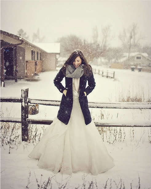 photo of winter bride pairs fit and flare wedding dress with deep navy coat