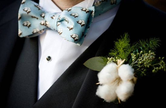 groom wears cotton boutonniere with patterned bow tie