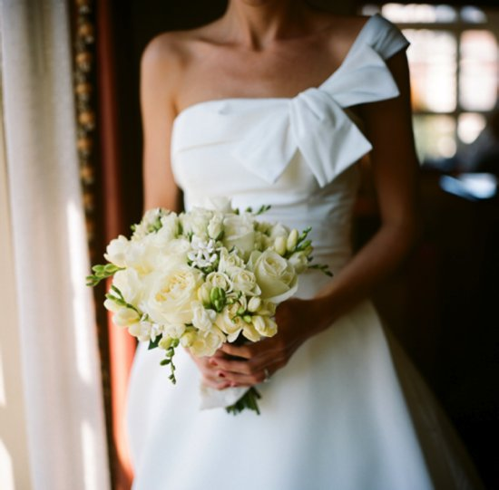 White one-shoulder wedding dress and ivory bridal bouquet