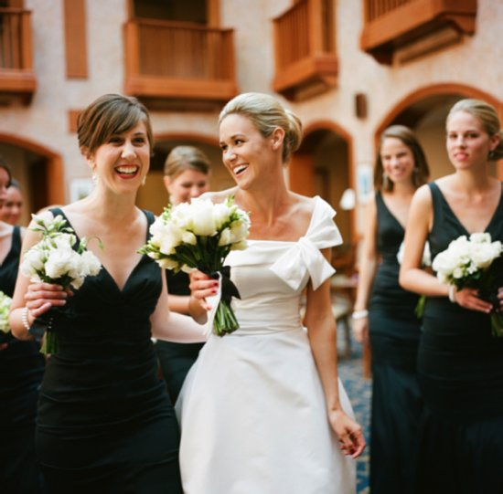 White one-shoulder wedding dress, black bridesmaids' frocks, white bouquets