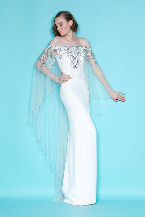 Ethereal white column bridal gown with sheer off-the-shoulder overlay cape