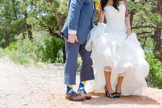 bride and groom show off colorful wedding shoes and socks