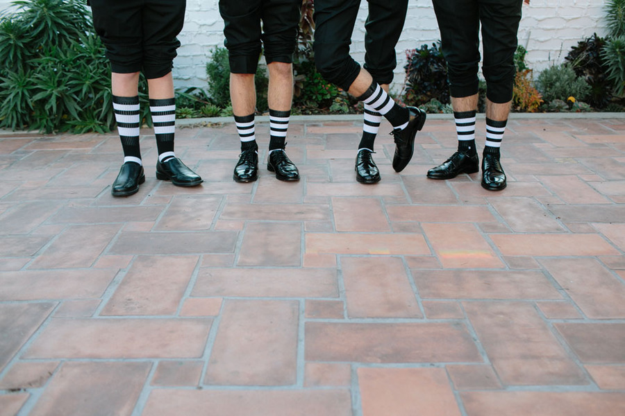groom and groomsmen wear funky black and white striped socks