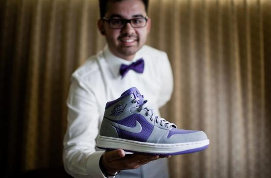 groom shows off purple and gray Nike wedding shoes