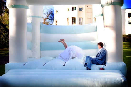 funny wedding photo of bride in bouncy castle
