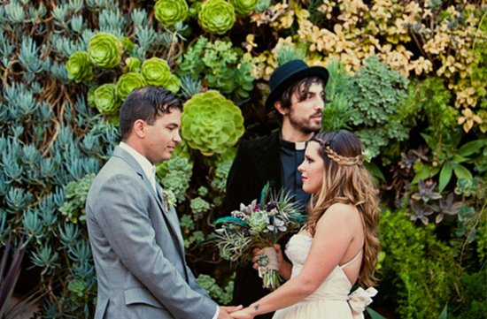 bride and groom vows with succulent wall as backdrop