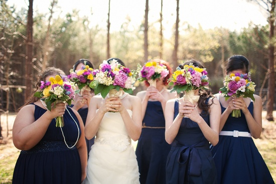 Bride and bridesmaids cover faces with bridal bouquets