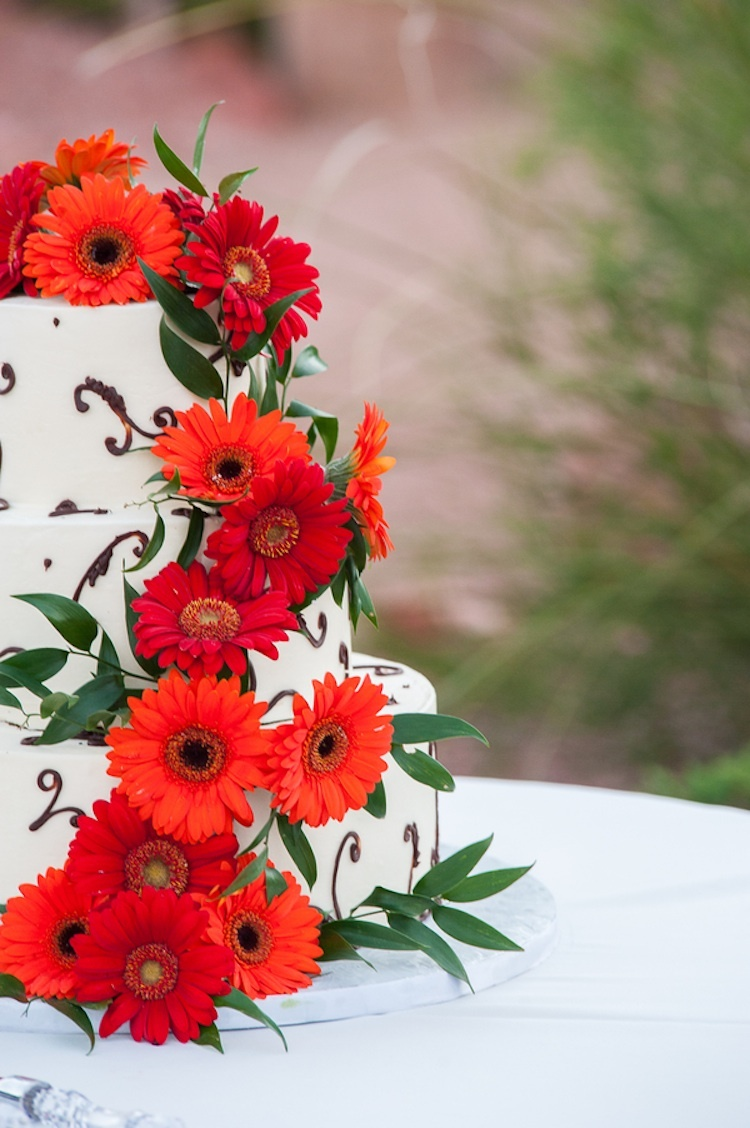 Birght_orange_and_red_blooms_on_white_wedding_cake.full