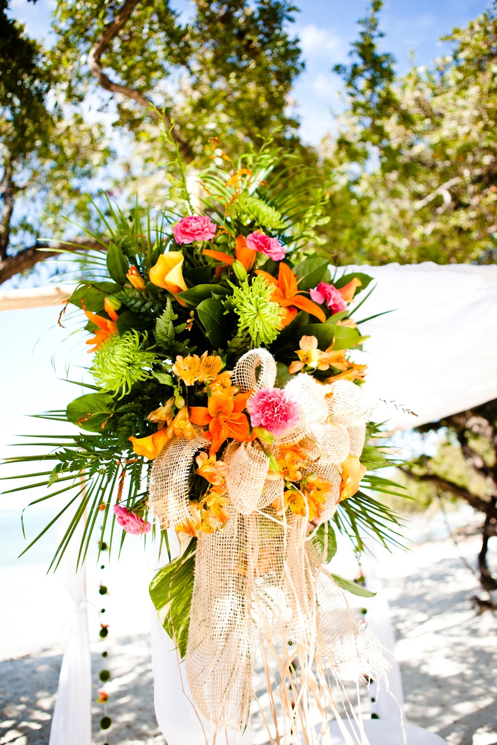 Tropical beach wedding ceremony with orange and pink wedding flowers