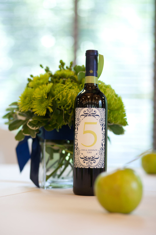 Florida wedding reception tables adorned with personalized bottles of wine and crisp green apples