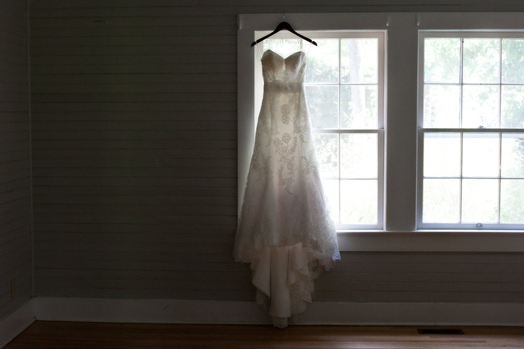 Classic and romantic ivory lace strapless wedding dress hangs in window