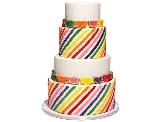 Classic white wedding cake adorned with multi-color stripes and candy fruit slices