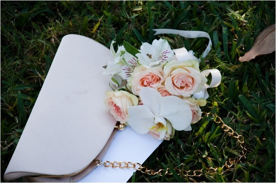 Romantic pastel wedding flowers and chic ivory bridal clutch