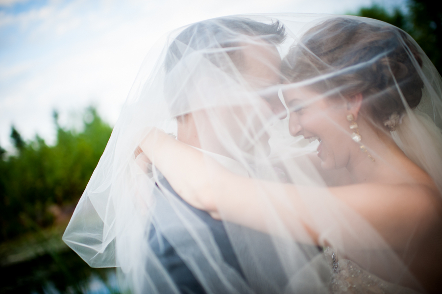 Real bride and groom embrace in veil