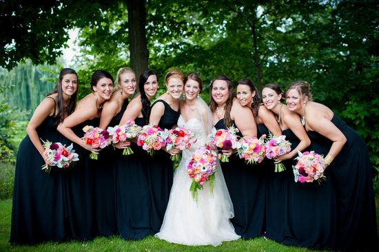 Bridemaids in long midnight blue dresses with bright bouquets
