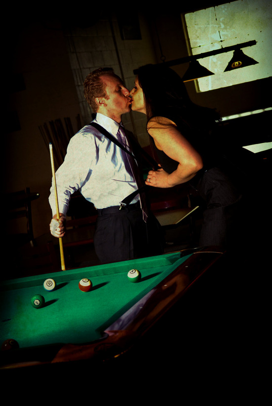 Chicago bride and groom-to-be pose and kiss during e-session at pool hall