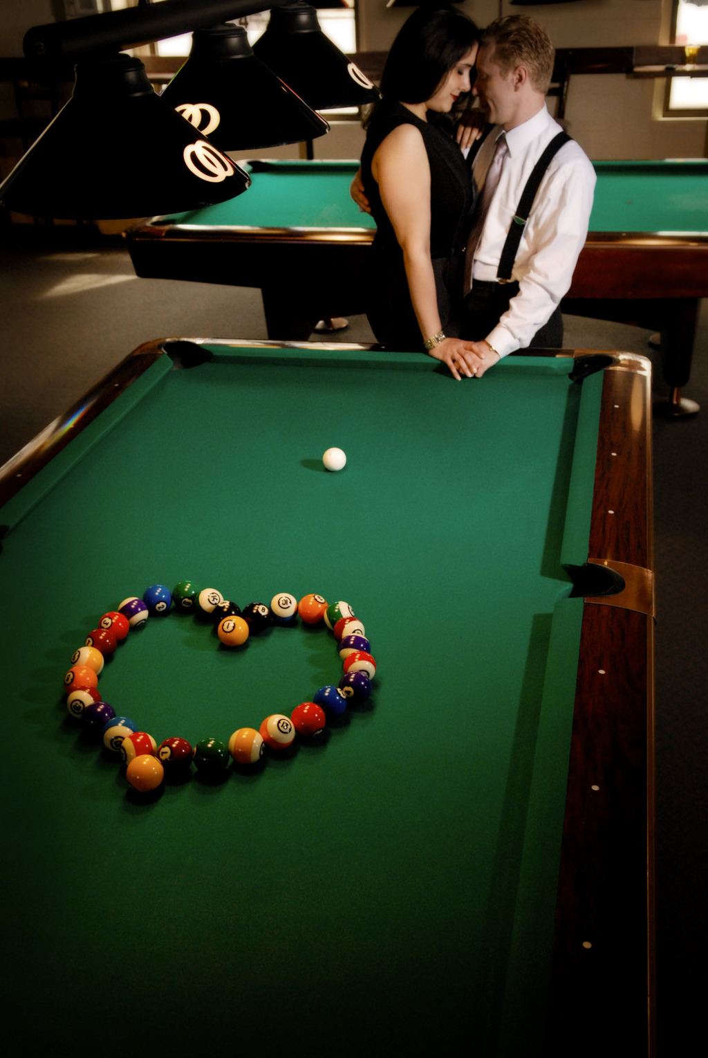 Bride and groom-to-be pose by billiard table, pool balls arranged in romantic heart shape