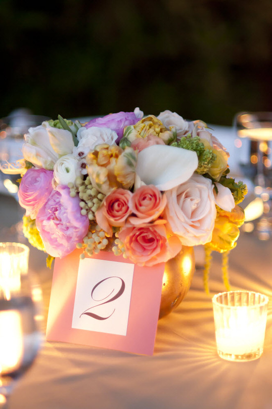Romantic outdoor wedding reception tablescape with pastel wedding flower centerpieces and candleligh