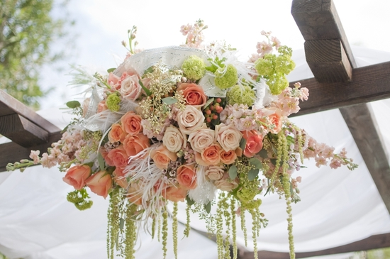 Romantic outdoor wedding ceremony arbor with peach, ivory and blush pink flowers