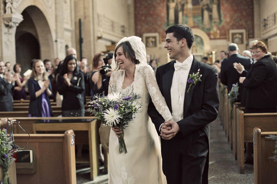 Bride in ivory lace wedding dress walks down ceremony aisle with groom after saying I Do