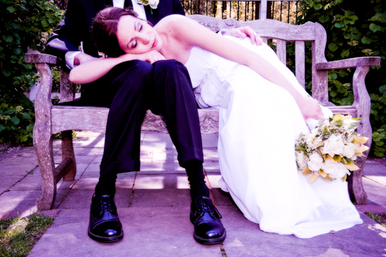 Gorgeous modern New Jersey bride in white strapless wedding dress lays head on grooms lap