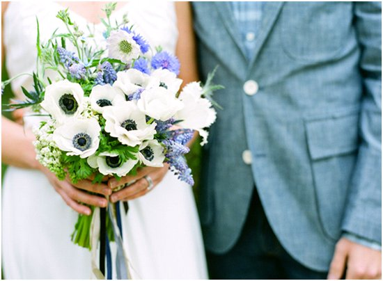Bride holds white and blue bridal bouquet, wears simple white empire wedding dress