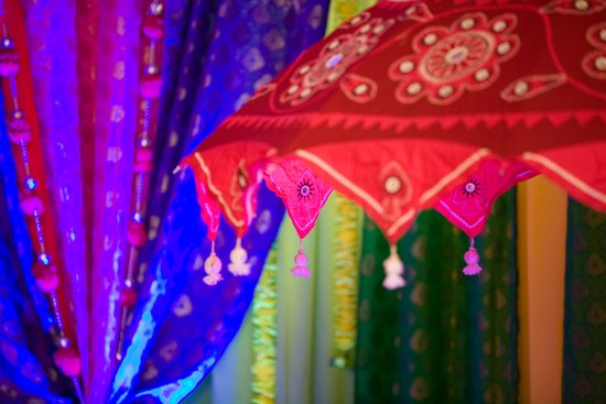 Ornate wedding umbrellas adorn reception room for Indian wedding