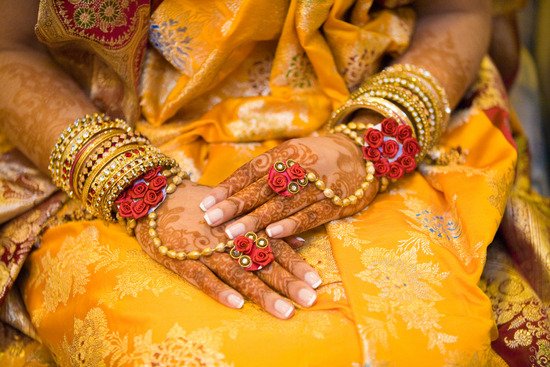 Gorgeous Indian bride wears traditional wedding sari and bridal henna