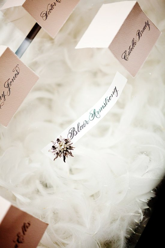 Vintage-inspired wedding reception decor with feathers and antique brooches