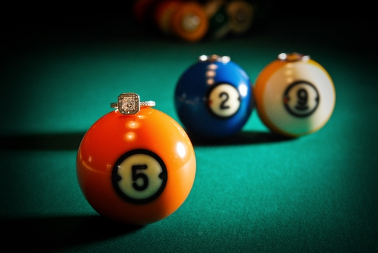 Artistic engagement session photo taken at a Chicago pool hall featuring the bride's engagement ring