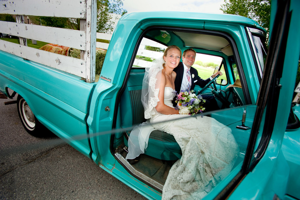 Bride and groom smile as they head to wedding reception in vintage pickup truck