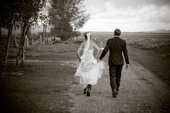 Beautiful bride and groom run hand in hand after saying I Do