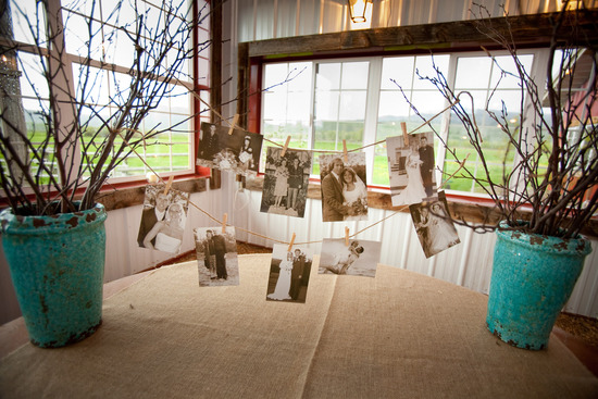 Antique photos hang from clothesline at rustic chic wedding reception