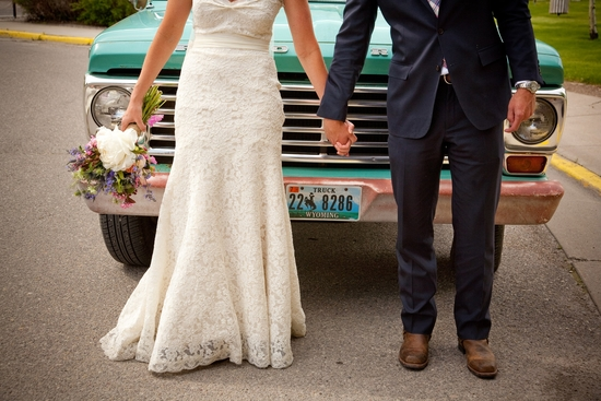 Bride in ivory lace wedding dress, groom in navy suit, hold hands in front of vintage pickup