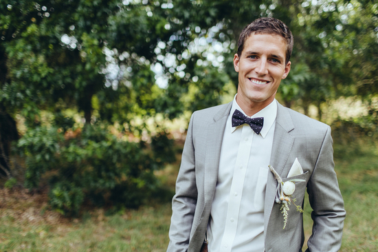 Groom in grey suit with black bow tie
