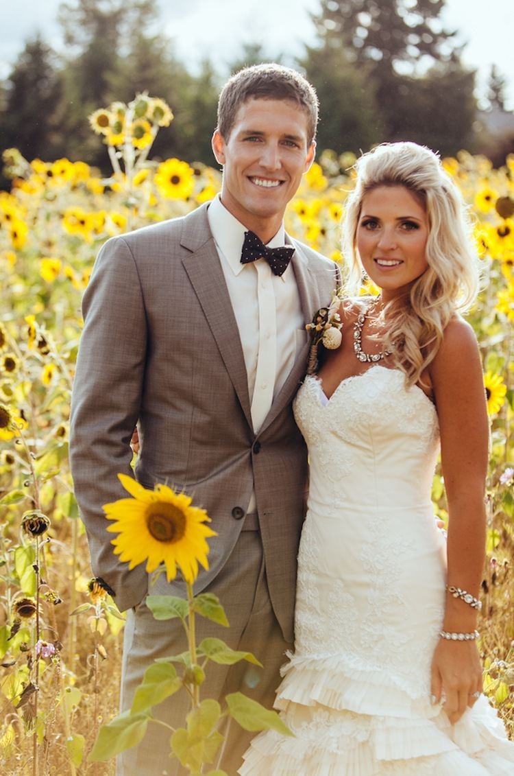Real wedding couple pose in sunflower field