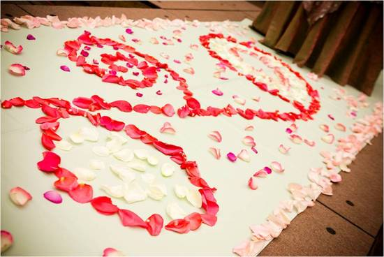 Wedding ceremony aisle covered in pink and red rose petals
