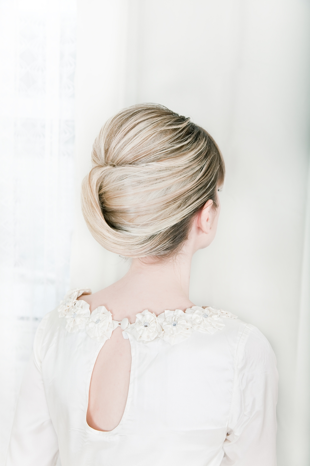 Sleek modern wedding updo with romantic lace wedding dress