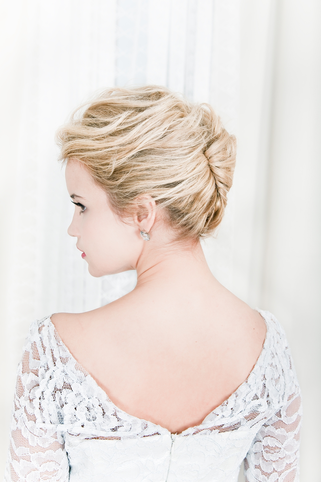 Sleek bridal updo, strapless wedding dress and layered pearl necklaces