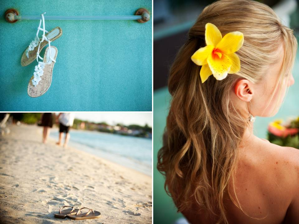 Beach bride's wedding sandals lay on the sand, bright yellow orchid in wedding hairstyle