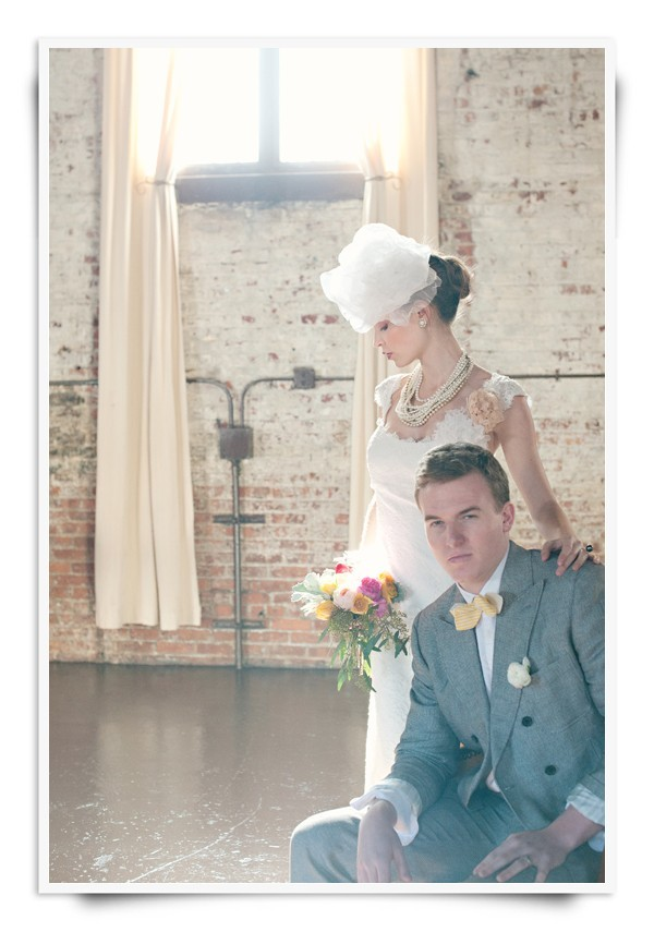 Vintage bride and groom- groom wears grey suit, yellow bow tie, bride in dramatic bridal veil