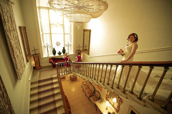 Bride walks down winding staircase of wedding venue to head to ceremony