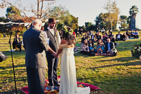 Bride and groom take vows, guests look on sitting on blankets in the park