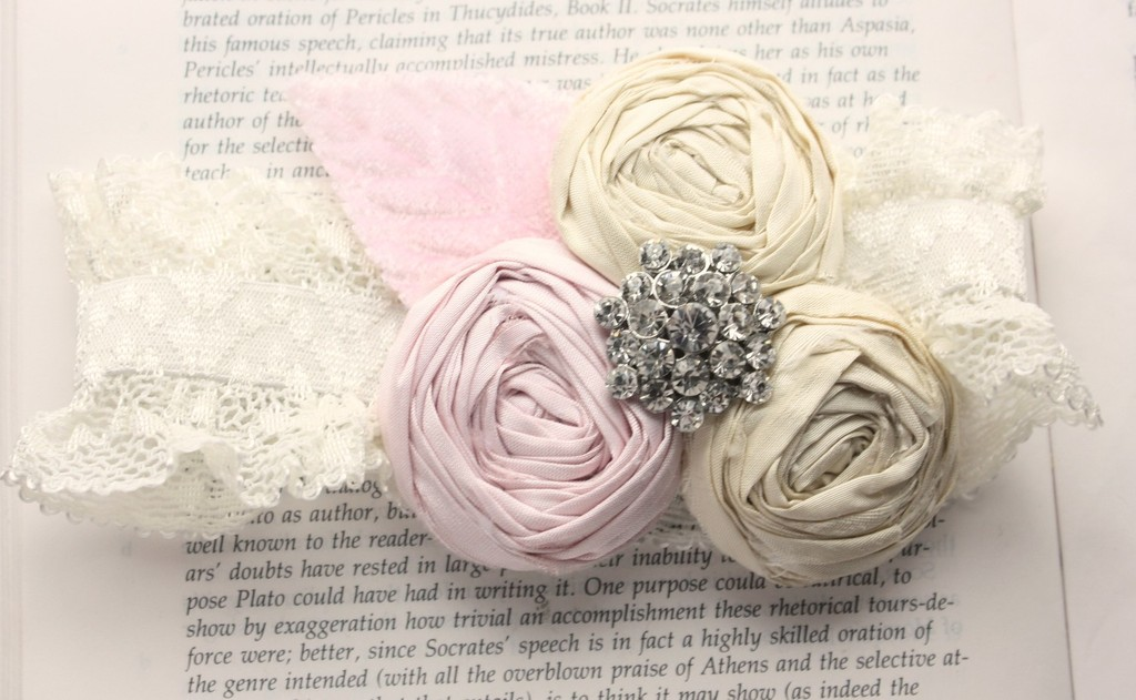 Custom bridal garter featuring lace band and handmade rosettes