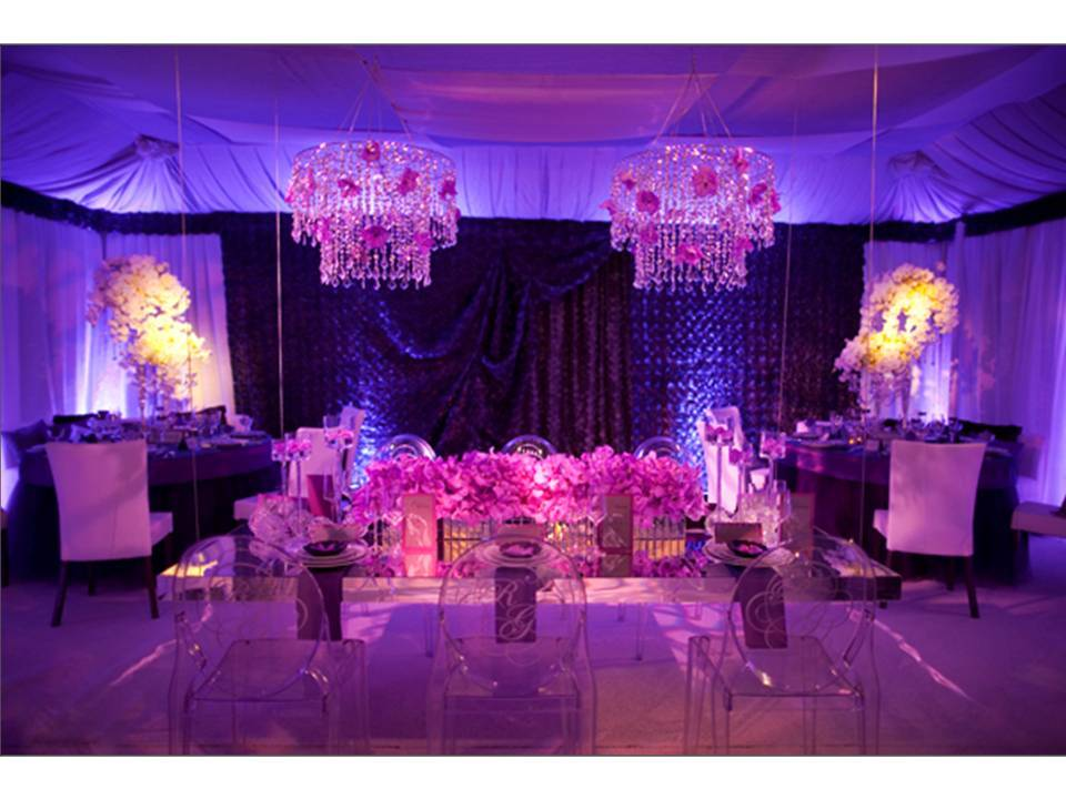 Glammed Up Wedding Reception Room With Purple Lighting And Orchids Ghost Chairs Chandeliers