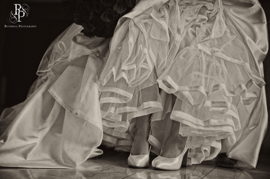 Artistic wedding photo- bride lifts up full tulle skirt of wedding dress to show off bridal heels