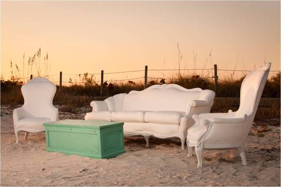 Vintage white lounge pieces for outdoor wedding reception on the beach
